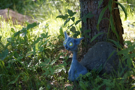 crochet: cat gray associated Interior walking toy crochet in the green grass of summer sunny day Stock Photo