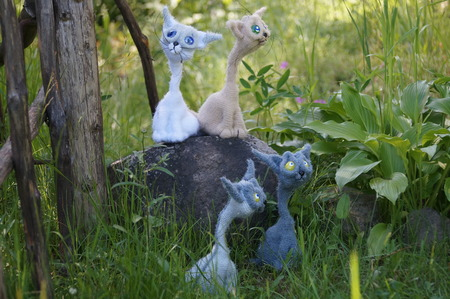 knitted toy Horde of multi-colored cats on a walk in the grass at the fence Stock Photo