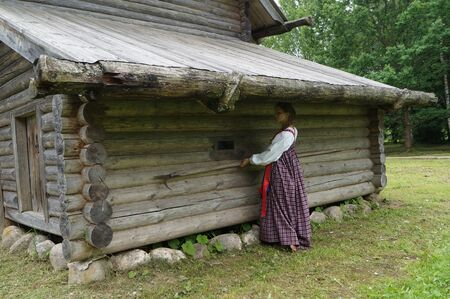 harpoon: the girl in the old village,pulls out from under the roof of the shed to stick a harpoon, heavy agricultural labor in Russia