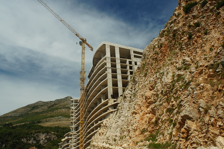 panning shot: the construction of the hotel in the rock by the sea, beach,stones,building construction crane