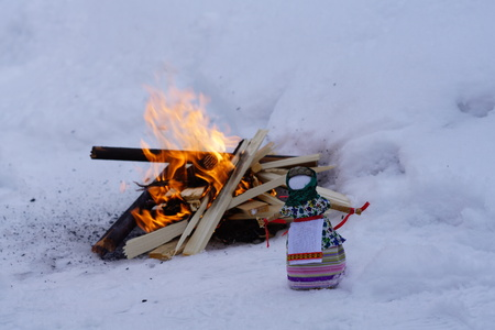 frock: carnival dolls on the background of burning fire in the winter on holiday Maslenitsa Stock Photo