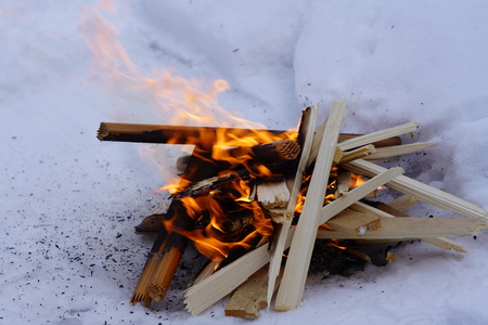 bonfire on the white snow in winter, fire and wood background Stock Photo