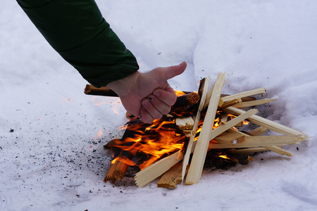 hand everythings fine in the background fire on the white snow in winter, fire and wood background Stock Photo