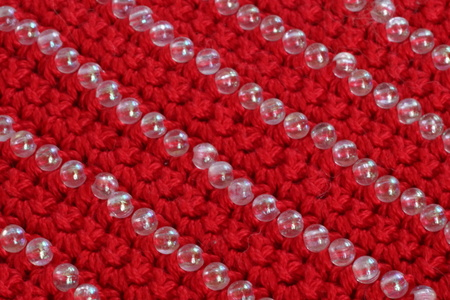 knitted fabric of red color with the decor of beads, red background Stock Photo