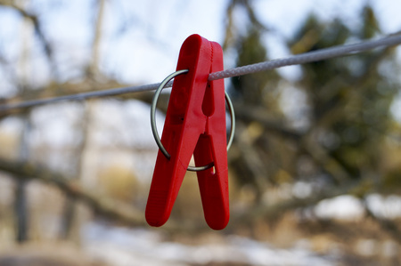 bonding rope: mount to hang linen and Old clothespins weigh on a twisted rope on the background of trees and blue sky Stock Photo