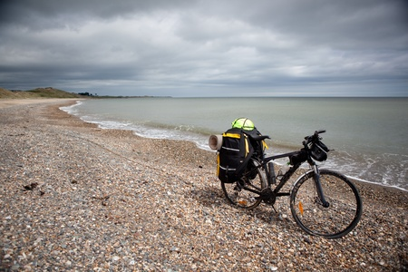Bicycle with bags, stand on coast line.