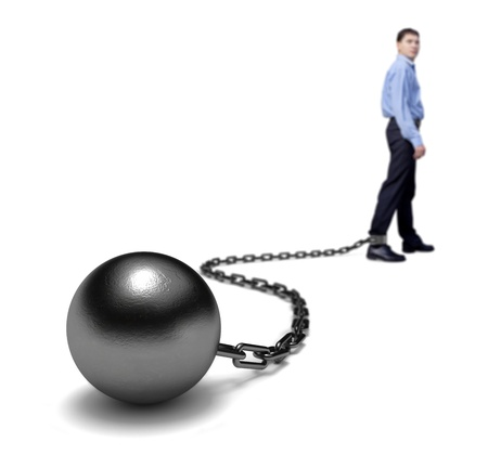 Mans legs dragging a ball and chain, selective focus. Stock Photo