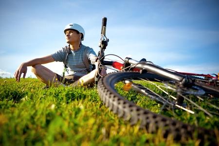 Mountain biker resting in a grass.
