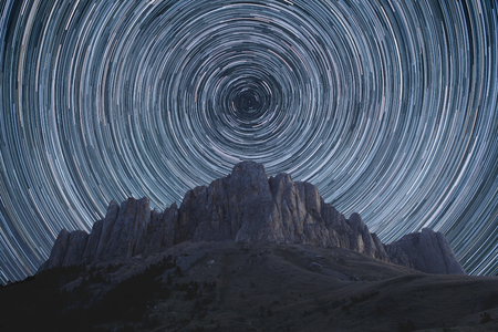 north star: Beautiful star trails over the rocky mountains. Polar North Star at the center of rotation.
