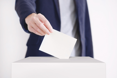 Man putting a ballot into a voting box.