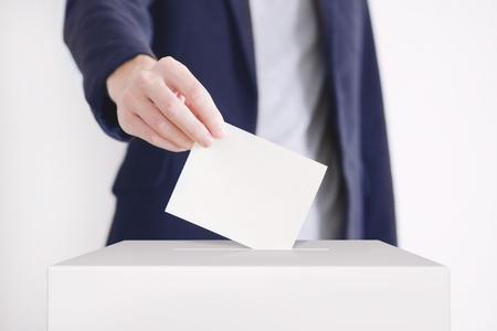 electing: Man putting a ballot into a voting box.