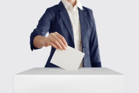 Woman putting a ballot into a voting box. Stock Photo
