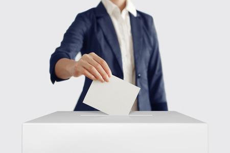 voting box: Woman putting a ballot into a voting box. Stock Photo