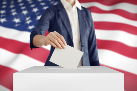 voting box: Woman putting a ballot into a voting box with USA flag on background.