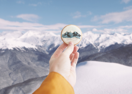 Holding ginger cookie with mountains print. Stock Photo