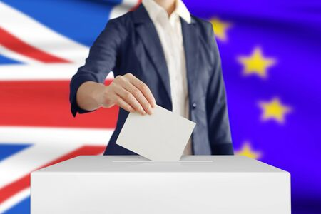 Brexit. Woman putting a ballot into a voting box with British and European Union flag on background. Imagens