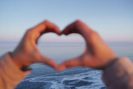 Hand shaped heart against frozen Baikal Lake. Banque d'images