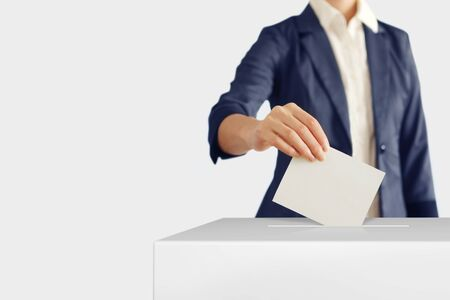 Woman putting a ballot into a voting box.