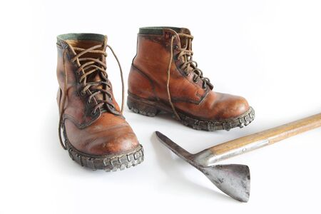 Old mountain boots and Ice Axe isolated on white.
