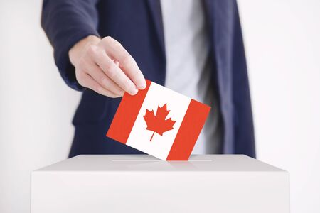 Man putting a ballot with Canadian flag into a voting box.