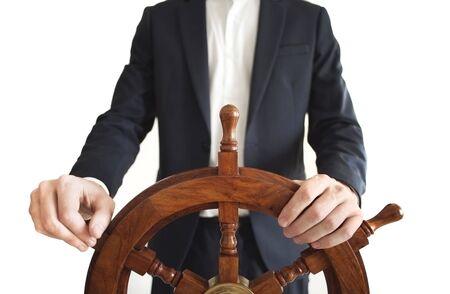 Businessman holding ship rudder. Standard-Bild