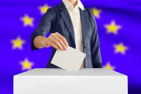 Woman putting a ballot into a voting box with European Union flag on background.