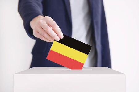 Man putting a ballot with German flag into a voting box.