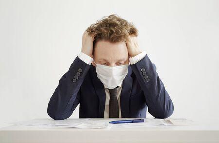 Stressed Businessman in Face Mask. Lockdown Coronavirus Concept.