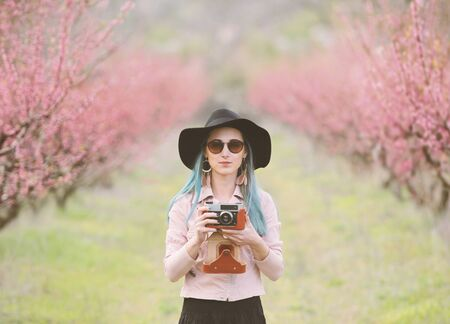 Girl with photo camera in blossom trees.