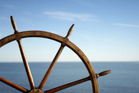 Ship wheel and blue sea on background.