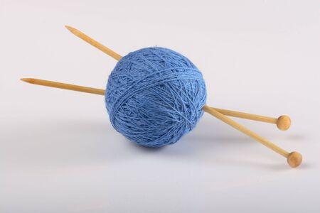Yarn and knitting needles on white background