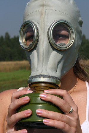 Girl in a gas mask on danger nature Stock Photo
