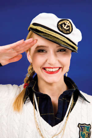Smiling blond young woman saluting in a sea peak-cap photo