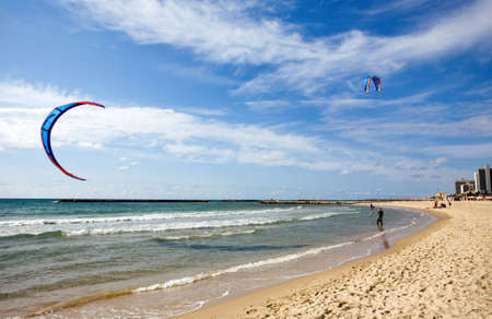 plucky: Two kitesurfers on the beach at Tel-Aviv, Israel