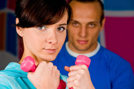 Woman at the health club with her personal trainer photo