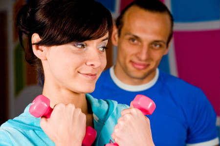 Smiling young woman at the health club with her personal trainer photo