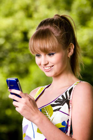 mobilephones: Smiling blond young woman with mobile phone outdoors