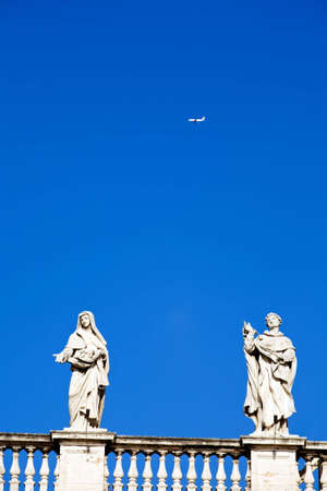 White classical statue of St. Peters Basilica in Vatican and flying air in blue sky, Rome, Italy photo