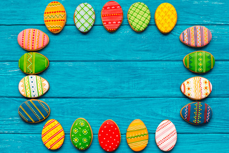 Colorful  small easter cookies on blue wooden background photo