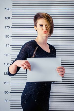 height measure: The girl with the short hair keeps a sign against the background on the height measure