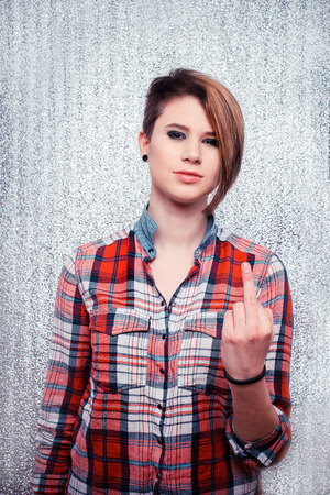 Girl with short hair in checkered shirt showing the finger on a silver background photo