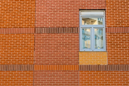 right side: Blue window on the right side on a red brick wall Stock Photo