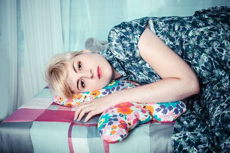memoirs: Beautiful girl lying down and hugging a cushion with buterffly shape Stock Photo