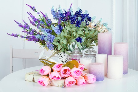 lavender: Still life of lavender flower tulips, candles and a book on light background Stock Photo