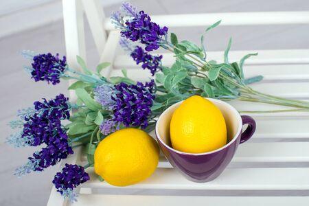 limón: Naturaleza muerta con limones frescos y lavanda en una vista superior silla blanca Foto de archivo