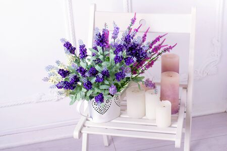 bailer: Still life of lavender flower and candles on a white chair on light background