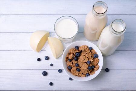 leche: Vista superior de un desayuno con copos de ma�z bayas azules y fres l�cteos sobre un fondo de madera blanca