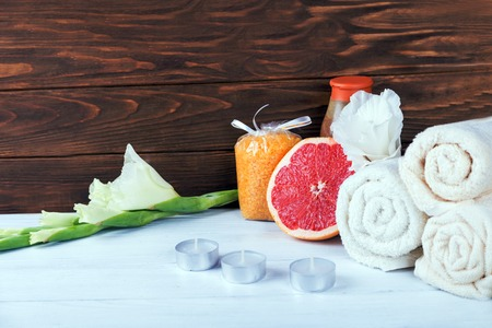 Composition of spa treatment on white wooden background with grapefruit, gladiolus, towels, bath bomb and candles on a brown wooden background. With copy space. Focus on grapefruit Stock Photo