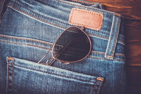Sunglasses in jeans back pocket  with brown leather tag retro vintage style with vignette