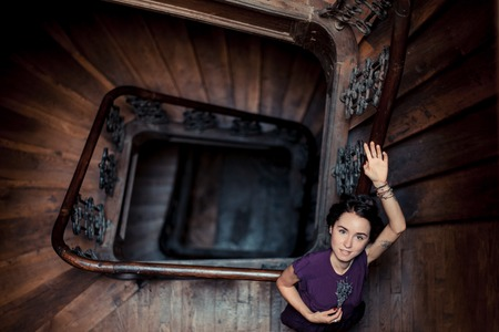 banisters: Portrait of a girl in romantic style lying on a banisters at spiral staircase in a ray of light, with tatoo and with lavender at her hand. Dark interior, toned and vintage picture.. Copy space. Stock Photo